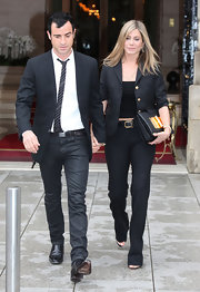 Jennifer Aniston complemented her suit with an embellished black leather clutch by Tom Ford.