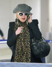 Cyndi Lauper talked on the phone while at LAX wearing a gray wool newsboy hat.