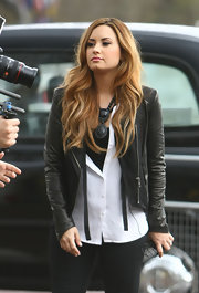 Demi Lovato accessorized with an eye-catching black pendant necklace for a tour of London.