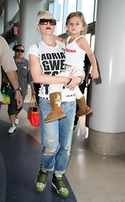 Gwen Stefani traded in her chic stilettos for a pair of green and white leather sneakers for a flight out of LAX.