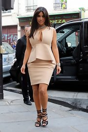 Kim Kardashian flaunted her assets in a plunging nude peplum dress while out and about in Paris.