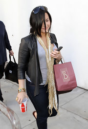 Demi Lovato styled her airport look with a tie-dye scarf.