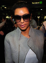 Kim Kardashian caught a flight out of O'Hare wearing a pair of Tom Ford gradient sunglasses in black and gray.