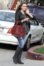 Lily Collins finished off her edgy look with a red Alexander Wang Rocco bag.