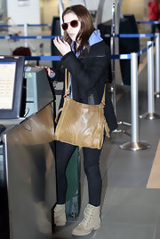 Anna Kendrick caught a flight to LA carrying a camel-colored leather shoulder bag.