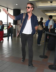 Ryan Gosling waved to at LAX while wearing a trusty denim zip-up.