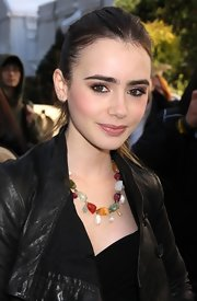 Lily Collins hit the Mercedes-Benz Fashion Week shows wearing a colorful gemstone beaded necklace.
