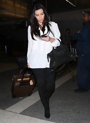 Kim Kardashian traveled in style with a Louis Vuitton rollerboard in tow.