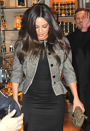 Mila Kunis styled her outfit with a metallic gold clutch.