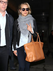 Taylor Schilling paired a gray scarf with a black moto jacket for her cozy airport look.