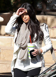 Kim Kardashian teamed a nude silk scarf with a white coat for her airport look.