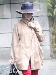 Katy Perry's purple straw hat added a summery touch to her rainy-day attire.