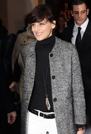 Ines de la Fressange accentuated her turtleneck top with a long necklace with an oversized crystal pendant at a Chanel fashion show.