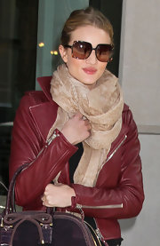Rosie Huntington-Whiteley added more warmth to her leather jacket with a snakeskin-print scarf during a night out in NYC.