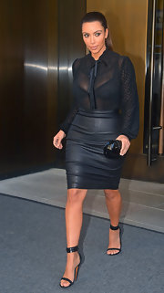 Kim Kardashian showed some skin in a sheer black button-down with a ruffle neckline and dotted sleeves.