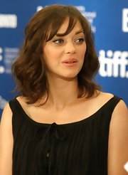 Marion Cotillard styled her hair with high-volume waves and wispy bangs for the 'Little White Lies' press conference.