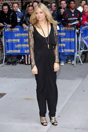 Sienna Miller posed outside the 'Letterman' studio wearing a draped black jumpsuit with a ruffle neckline.