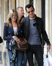Jennifer Aniston strolled through Paris carrying a zip-embellished brown leather bag by Tom Ford.