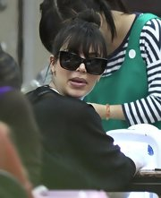Kim Kardashian hid her eyes behind a pair of rectangular cateye sunnies while having her nails done.