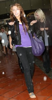 Miley Cyrus matched her tee with a purple leather hobo bag by Bottega Veneta.
