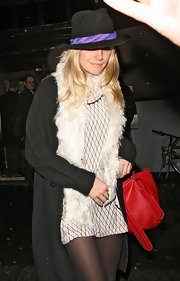 Sienna Miller enjoyed a night of clubbing wearing a long black cardigan styled with a white fur scarf.