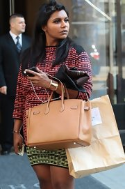 Mindy Kaling accessorized with an elegant gold cuff while out and about.