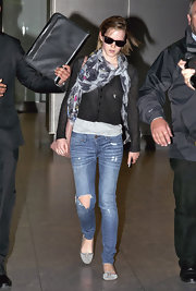 Emma Watson teamed a black Opening Ceremony cardigan with a patterned scarf for a cozy airport look.