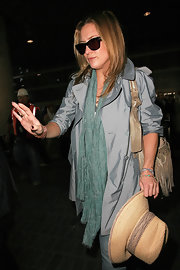 Kate Hudson adorned her outfit with a green plaid scarf for her flight.