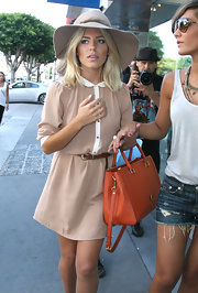 Mollie King's orange MCM tote added a dazzling pop of color to her neutral-toned outfit.