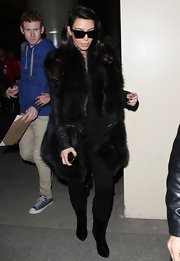 Kim Kardashian arrived at LAX looking posh in black suede boots and a fur coat.