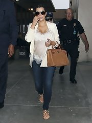 Kim Kardashian chose a pair of Gucci thong sandals to complete her airport outfit.