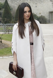 Mila Kunis attended the Dior fashion show carrying a croc-embossed clutch from the label.