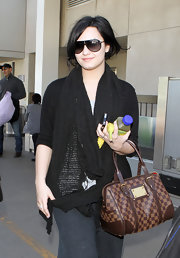 Demi Lovato emerged from LAX bundled up in a black knit scarf.
