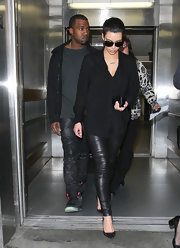 Kim Kardashian was edgy in a black button-down and leather skinnies while catching a flight at LAX.