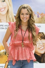 Miley Cyrus accessorized with a cute peace-sign-and-tree pendant necklace by Gypsy 05 at the Rome photocall for 'Hannah Montana: The Movie.'