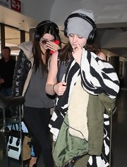 Kylie Jenner accessorized with a gray knit beanie for a flight.