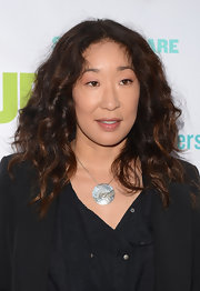 Sandra Oh styled her black outfit with a silver disc pendant.