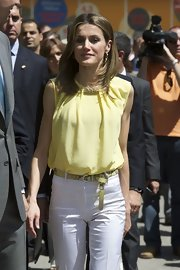Princess Letizia matched a yellow snakeskin belt with white slacks and a sleeveless blouse for the Madrid Book Fair.
