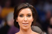 Kim Kardashian styled her hair into a mildly messy, loose updo for an NBA game.