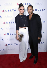 Chrissy Teigen bared a bit of tummy in a black crop-top when she attended Delta Air Lines' celebration of its new terminal.
