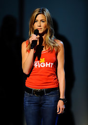 Jennifer Aniston teamed her tank with blue jeans and a black leather belt.