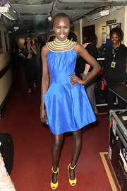 Alek Wek paired yellow ankle-strap peep-toes with her dress for a color-blocked finish.