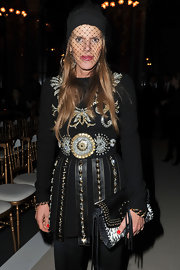 Anna dello Russo attended the Balmain fashion show wearing a glammed-up veiled beanie by Jil Sander.
