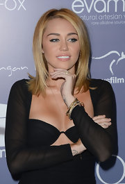 Miley Cyrus teamed some gold bangles with a black cutout dress for the Australians in Film Awards.