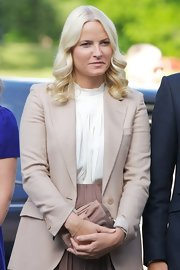 Princess Mette-Marit accessorized with a bowed brown leather clutch at the opening of the 'Landskap og Rom' exhibition.