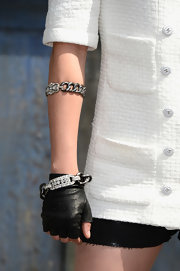Kristen Stewart went for edgy styling with a pair of fingerless leather gloves at the Chanel Couture Fall 2013 show.