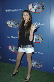 Miley Cyrus teamed her top with white short shorts.