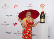 Cyndi Lauper signed a Moet & Chandon Imperial bottle at the Kentucky Derby wearing a floral dress.