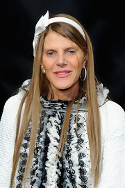 Anna dello Russo accessorized with a bow-adorned Louis Vuitton headband for a youthful touch during the Chanel fashion show.