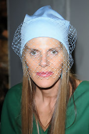 Anna dello Russo attended the Bottega Veneta fashion show wearing her trademark Jil Sander veiled beanie in pastel blue.